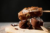 closeup of some chocolate ice cream bars on a chopping board, placed on a rustic wooden table sprink poster