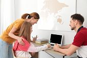 Parents Helping Their Teenager Daughter With Homework Indoors poster
