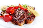 Steak with vegetables on white plate