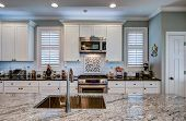 Luxury kitchen remodel with granite island in foreground. poster