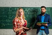Male Teacher With Students. Young Attractive Teacher Pointing At Chalkboard. Sexy Female Student Poi poster