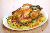 Whole roasted chicken with vegetables and rosemary