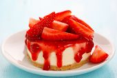 Cheesecake with fresh strawberries on white plate closeup