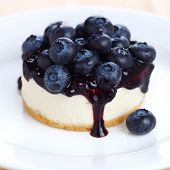 Cheesecake with fresh blueberries on white plate closeup
