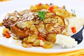 Chicken breast baked with almonds and apricot sauce on white plate, soft focus
