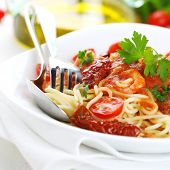 Spaghetti with sun dried tomatoes and tomato sauce on white plate