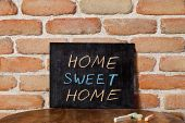 Black chalkboard with the phrase HOME SWEET HOME drown by hand on wooden table on brick wall backgro poster