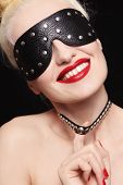 Portrait of young beautiful smiling woman in studded blindfold and collar