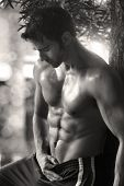 Sexy sensual outdoor portrait of a very fit male model shirtless showing abs