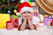 Little girl near the Christmas tree in festively decorated room