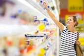 foto of grocery cart  - Beautiful young woman shopping for diary products at a grocery store - JPG