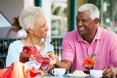 Senior Couple Enjoying Snack At Outdoor Cafe After Shopping