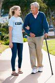 Teenage Volunteer Helping Senior Man Walking Through Park