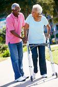 Senior Man helfen Frau mit Walking Frame
