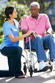 Carer Pushing Unhappy Senior Man In Wheelchair
