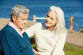 Mujer Senior reconfortante deprimido esposo sentado en la banca