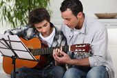 stock photo of preteen  - Father teaching son the guitar - JPG