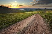 daybreak on a dirt road in a meadow of the sicilian countryside