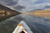 expedition decked canoe and wooden paddle on a narrow mountain lake - Horsetooth Reservoir near Fort Collins, Colorado, late fall scenery