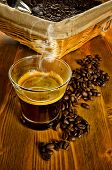 Cup of coffee with coffee beans and basket on background