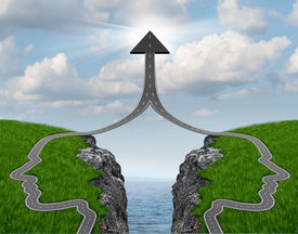 stock photo of merge  - Bridge the gap and bridging the differences between two business partners over a financial cliff to merge together for team success as a strong partnership with two head shaped roads merging as an upward arrow - JPG