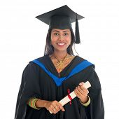Happy Indian university student in graduation gown and cap holding diploma certificate. Portrait of mixed race Asian Indian and African American female model standing isolated on white background.