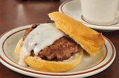 stock photo of biscuits gravy  - A sausage patty on a fresh baked biscuit with country gravy - JPG