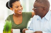 stock photo of grandfather  - smiling elderly african american man enjoying coffee with his granddaughter at home - JPG