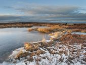 a frozen peat pond on moorland in the south pennines.