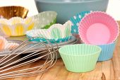 Variety of cupcake liners in different colors with a muffin pan and wire whisk
