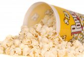Container of delicious movie popcorn with popcorn spilling out