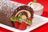Delicious Christmas Buche de Noel cake with raspberries, whipped cream and powdered sugar