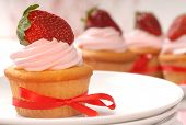 Delicious vanilla cupcake with strawberry frosting and a fresh strawberry