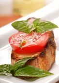 Delicious bruschetta topped with fresh tomato, Parmigiano-Reggiano cheese and basil