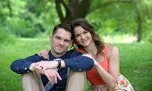 Happy young couple sitting on the ground under a tree in a garden setting