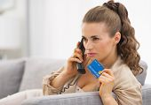 Concerned Young Woman With Credit Card Talking Phone