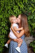 stock photo of mater  - Mother holds daughter in his arms and kisses her on the cheek - JPG