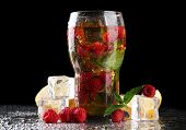 Iced tea with raspberries and mint on dark background with yellow light