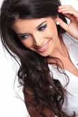 closeup picture of a young beautiful woman looking down and smiling while holding her hand behind her ear. isolated on a white background