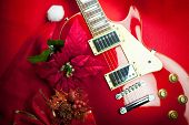 Red electric guitar with christmas ornaments. Concept image for christmas / holiday season music event, or musical instrument for Christmas present.