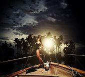 Young sexy woman on her private yacht at sunset around tropical island