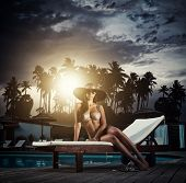Young glamour woman by the swimming pool at tropical resort