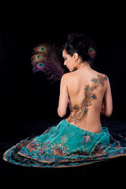 stock photo of female peacock  - Profile portrait of beautiful brunette woman sitting on the ground and holding three peacock feathers - JPG