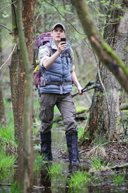 image of boggy  - lost hiker in forest with mobile satellite navigation device  - JPG