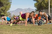 image of lady boots  - Cheerful blond fitness instructor leading group in push - JPG