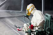 foto of air paint gun  - painter painting metal designs with airbrush on factory - JPG