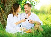 Beautiful Young Couple Having Picnic in Countryside. Happy Family Outdoor. Smiling Man and Woman relaxing and drinking Wine in Park. Relationships