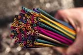 Artistic group of colorful incense sticks held in hand.