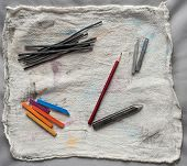 Artistic drawing and sketching tools on canvas support.