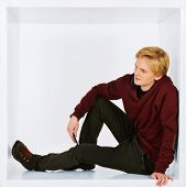image of restriction  - Young man in casual clothes sitting in white cube - JPG